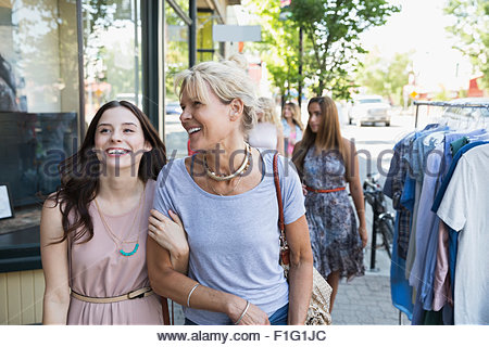 Smiling mother and daughter walking arm in arm - Stock Photo