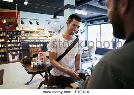 Man paying worker with credit card in shop - Stock Photo