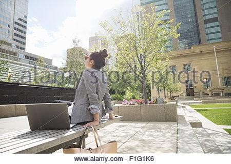 Businesswoman basking in sunshine in urban park - Stock Photo