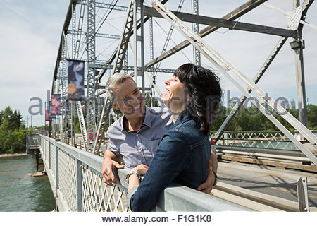 Laughing couple on bridge over river - Stock Photo