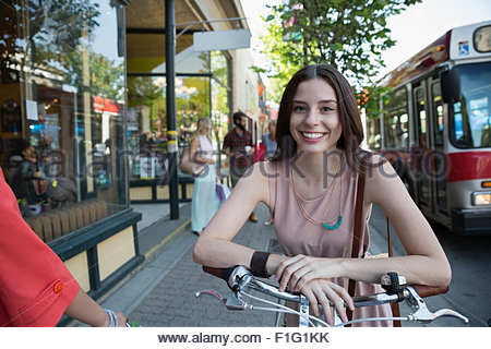 Portrait smiling woman on bicycle at storefront - Stock Photo