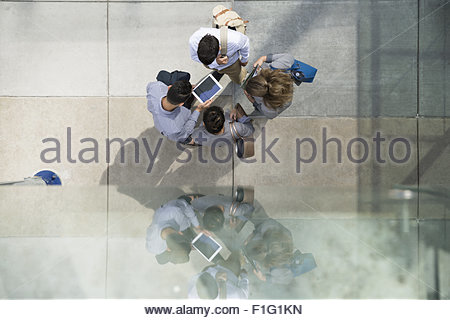 Overhead view business people using digital tablet - Stock Photo
