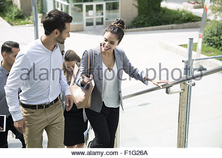 Business people talking and ascending stairs - Stock Photo