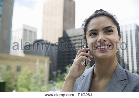 Close up businesswoman talking on cell phone city - Stock Photo