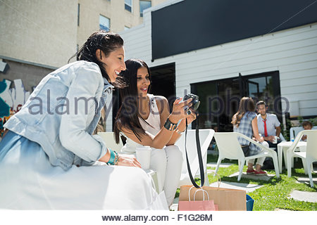 Women viewing photos digital camera on sunny photo - Stock Photo