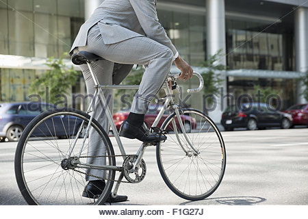 Businessman in suit riding bicycle on city street - Stock Photo