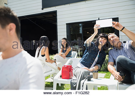 Couple taking selfie with digital tablet on sunny patio - Stock Photo