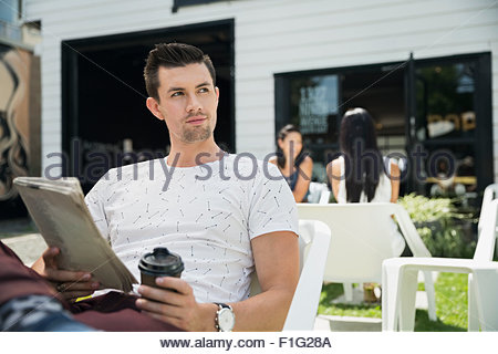 Man with coffee and newspaper looking away patio - Stock Photo