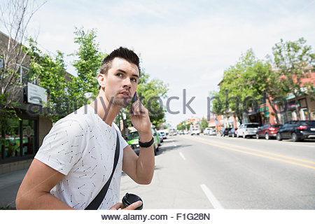 Man talking and cell phone crossing sunny street - Stock Photo