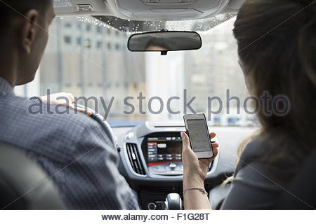 Businesswoman carpooling using cell phone in car - Stock Photo