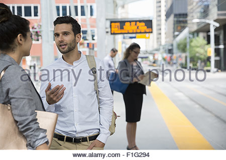 Business people talking and waiting train station platform - Stock Photo