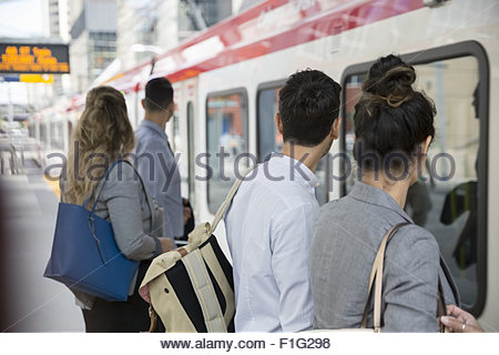 Business people waiting to board train on platform - Stock Photo