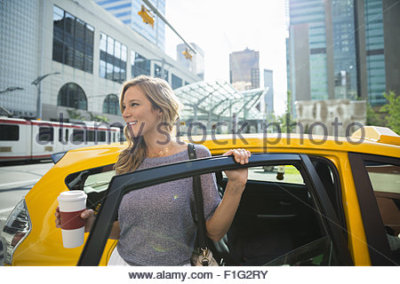 Businesswoman with coffee getting out of taxi - Stock Photo