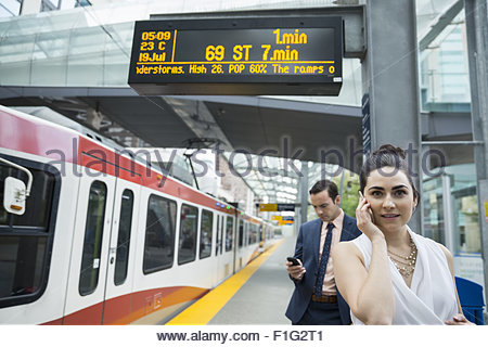 Business people waiting at train station platform - Stock Photo
