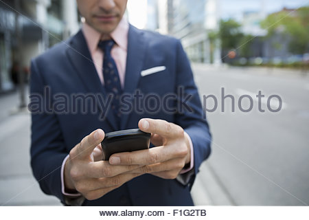 Close up businessman texting cell phone city street - Stock Photo