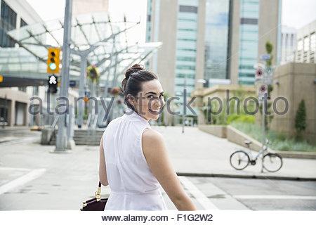Portrait confident businesswoman turning crossing urban crosswalk - Stock Photo