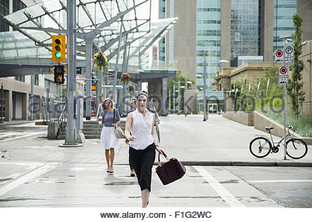 Businesswoman rushing in crosswalk in urban street - Stock Photo