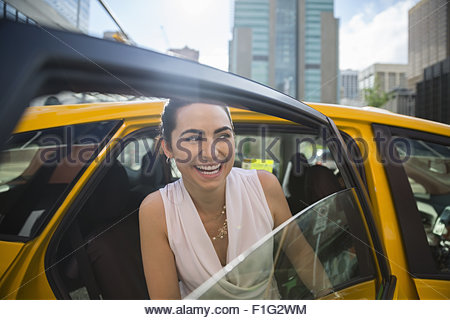 Smiling businesswoman getting out of taxi in city - Stock Photo