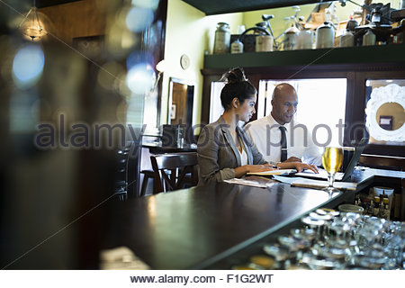 Business people working at laptop in pub - Stock Photo