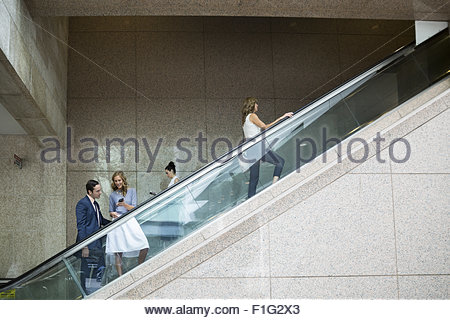 Business people riding escalator - Stock Photo