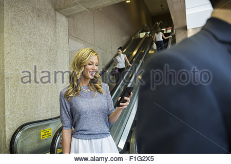 Businesswoman texting with cell phone near escalator - Stock Photo