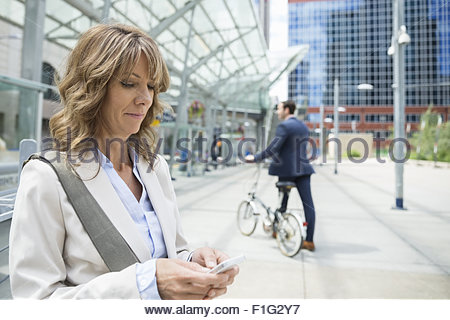 Smiling businesswoman texting on cell phone train station - Stock Photo