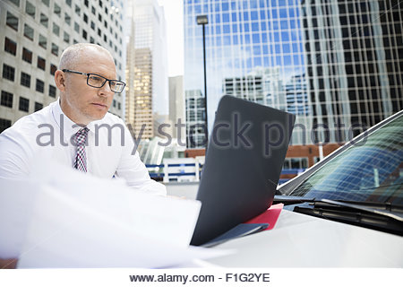 Businessman using laptop on car in city - Stock Photo