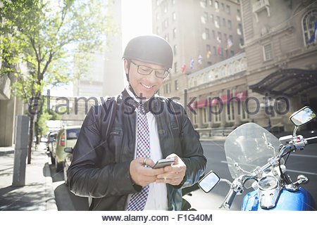 Businessman commuting on motorcycle texting with cell phone - Stock Photo