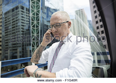 Businessman on cell phone checking wristwatch in city - Stock Photo
