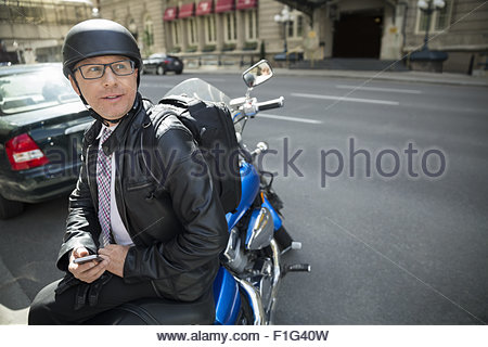 Businessman commuting on motorcycle - Stock Photo