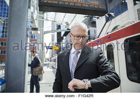 Businessman checking the time on wristwatch at train station - Stock Photo