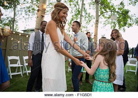Bride and flower girl dancing backyard wedding reception - Stock Photo