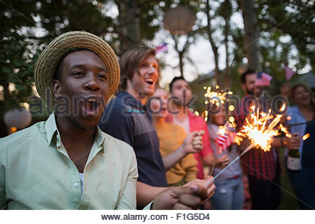 Friends with sparklers cheering 4th of July party - Stock Photo