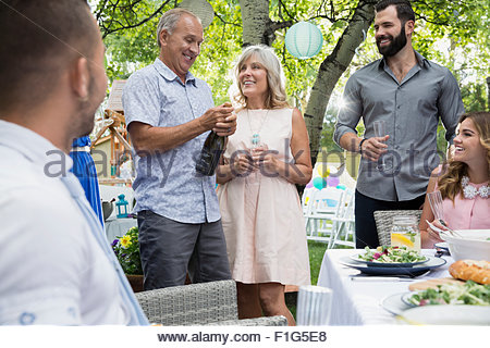 Senior couple opening champagne bottle garden party lunch - Stock Photo