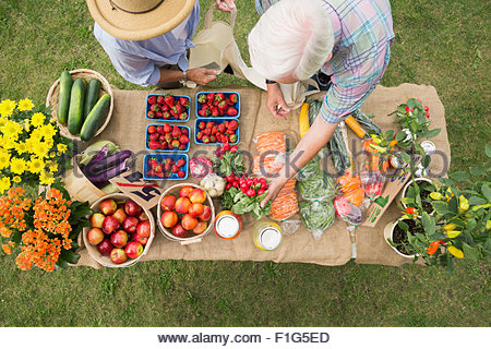 Shoppers reaching produce on farmers market display table - Stock Photo