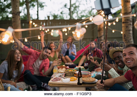 Friends dinner party taking selfie with selfie stick - Stock Photo
