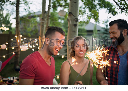 Friends with sparklers at backyard party - Stock Photo