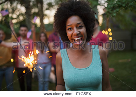 Portrait enthusiastic woman with sparkler in backyard - Stock Photo