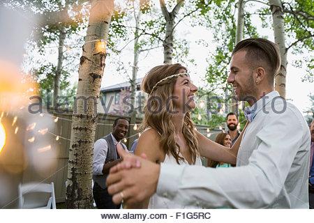 Bride and groom dancing at backyard wedding reception - Stock Photo