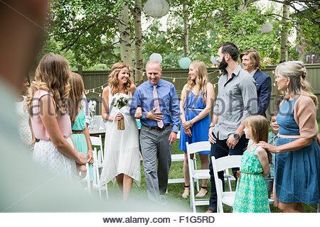Bride and father walking down aisle backyard wedding - Stock Photo