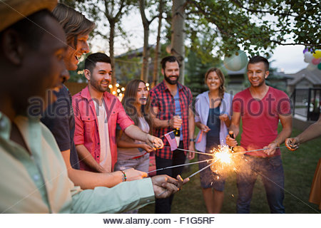 Friends lighting sparklers backyard 4th of July party - Stock Photo
