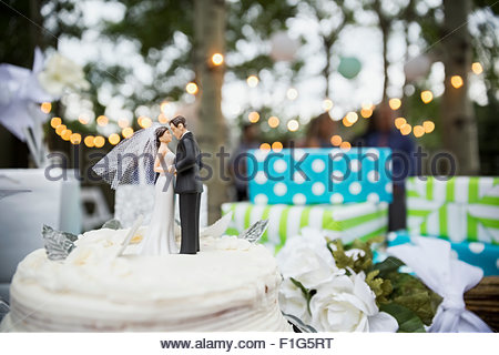 Bride and groom cake topper on cake - Stock Photo