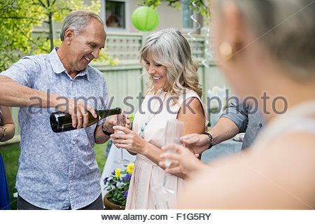 Husband pouring champagne for wife at garden party - Stock Photo