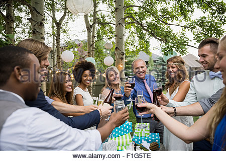Bride, groom and wedding guests toasting drinks reception - Stock Photo