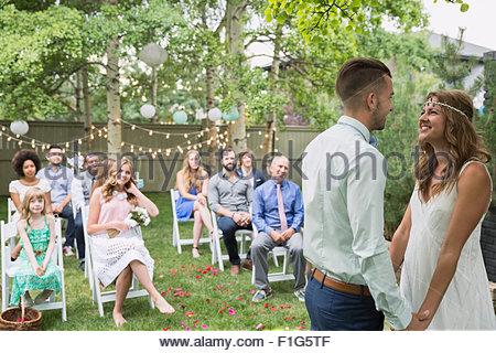 Wedding guests watching bride and groom backyard wedding - Stock Photo