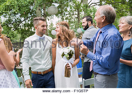 Guests clapping for bride and groom backyard wedding - Stock Photo