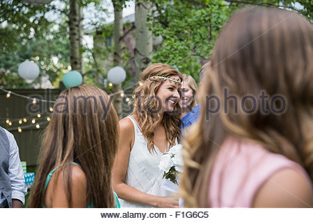 Smiling bride walking down aisle at backyard wedding - Stock Photo