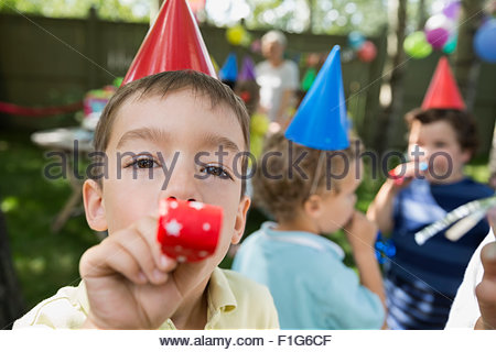 Portrait boy blowing birthday party favor - Stock Photo
