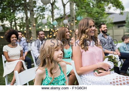 Smiling wedding guests enjoying backyard wedding - Stock Photo