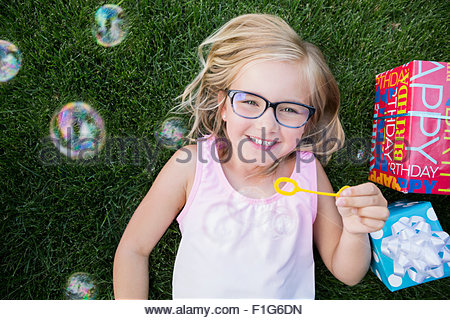 Overhead view portrait smiling girl blowing bubbles - Stock Photo
